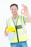 Carpenter holding gloves and hardhat while gesturing OK Stock Images