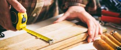 Carpenter holding a measure tape Stock Photo
