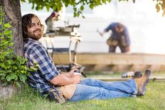 Carpenter Holding Mobilephone And Cup While. Side view portrait of happy carpenter holding mobilephone and disposable cup while leaning on tree trunk Royalty Free Stock Images