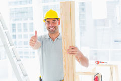 Carpenter holding plank while gesturing thumbs up in building Stock Photo