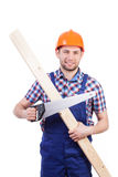 Carpenter holding plank and saw Royalty Free Stock Photos
