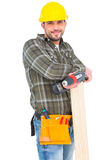 Carpenter holding power drill and wood plank. On white background Royalty Free Stock Photos