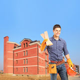 Carpenter holding sills with an apartment block Royalty Free Stock Photos