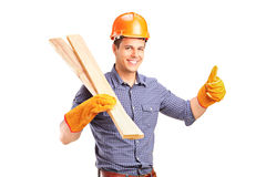 A carpenter holding sills and giving thumb up. A smiling manual carpenter holding sills and giving thumb up isolated on white background Royalty Free Stock Images
