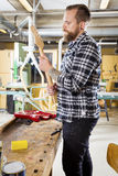 Carpenter inspects a wooden guitar neck in workshop Royalty Free Stock Photography