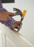 Carpenter installer with hammer and chisel at wood door Royalty Free Stock Photos