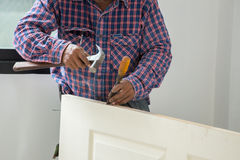 Carpenter installer with hammer and chisel at wood door Stock Photo