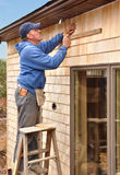 Carpenter installing cedar shingles. On side walls of new house royalty free stock photography