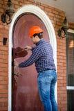 Carpenter installing lock at big metal door Royalty Free Stock Photo