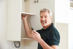Carpenter Installing Luxury Fitted Kitchen Stock Photography