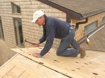 Carpenter installing sheathing to roof. Carpenter installing plywood sheathing to roof of addition stock photo