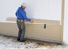 Carpenter installing siding. Carpenter using gauge to install fibrous cement siding stock photos