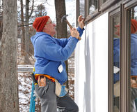 Carpenter installing windows. In an addition stock image