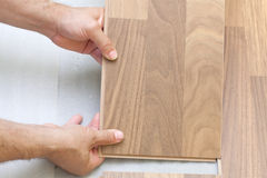 Carpenter installing wooden floor Royalty Free Stock Photos