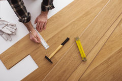 Carpenter installing a wooden flooring. And measuring with a precision ruler, top view Royalty Free Stock Photos
