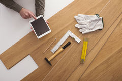Carpenter installing a wooden floring and using a tablet stock image