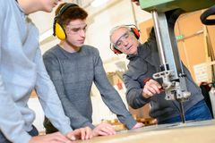 Carpenter instructor with students in workshop. Stuents royalty free stock photo