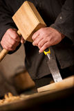 Carpenter or joiner using a chisel and mallet. Close up of the hands of a carpenter or joiner using a chisel and wooden mallet to cut and shape a piece of wood Stock Image