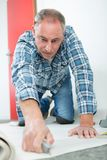Carpenter joiner worker preparing door frame for indoor installation. Handyman royalty free stock image