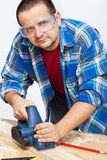 Carpenter or joiner working with electric planer. On workbench Stock Photography