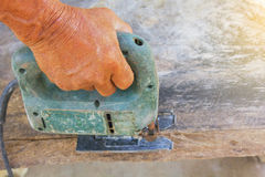 Carpenter or joiner working with electric saw - closeup on hands,Carpenter on nature,Carpenter in thailand,Carpenter in asia.  Royalty Free Stock Images