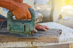 Carpenter or joiner working with electric saw - closeup on hands,Carpenter on nature,Carpenter in thailand,Carpenter in asia Stock Image