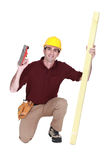 Carpenter kneeling with wood Royalty Free Stock Photo