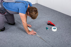 Carpenter Laying Carpet. Carpenter In Overall Crouching Laying Carpet On Floor At Home stock images
