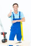 Carpenter leaning on spirit level while gesturing thumbs up Royalty Free Stock Images