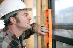 Carpenter Leveling Window. A horizontal view of a carpenter checking a newly installed window to see if it's level.  Authentic and accurate content Royalty Free Stock Images