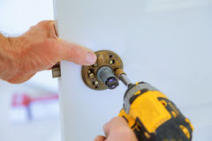 Carpenter lock installation with electric drill into interior wood door. Carpenter at lock installation with electric drill into interior wood door Royalty Free Stock Image
