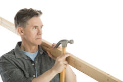 Carpenter Looking Away While Holding Hammer And Wooden Plank. Male carpenter looking away while holding hammer and wooden plank against white background Royalty Free Stock Photography