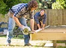Carpenter Looking At Coworker While Assisting Him Stock Image