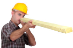 Carpenter looking down at wooden plank Royalty Free Stock Photography