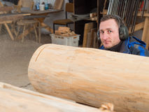 Carpenter looking to the camera behind a tree trunk Stock Images