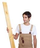 Carpenter looking at wooden beam Stock Photo
