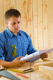 Carpenter looks on the blueprint Royalty Free Stock Photography