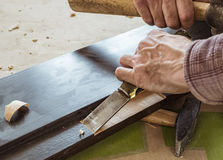 Carpenter. Makes a chisel recess in the door unit Royalty Free Stock Photo