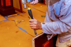 Carpenter makes a hole in wooden door for the mortise lock with a hammer and chisel. Carpenter makes a hole in new wooden door for the mortise lock with a royalty free stock photos