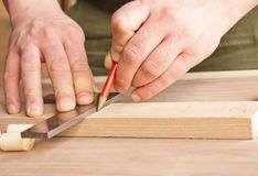 Carpenter makes markings in red pencil . Carpenter makes markings in red pencil Stock Image