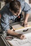 Carpenter making furniture. Young carpenter making furniture to new house Royalty Free Stock Photo