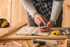 Carpenter making project calculation using smartphone app. In small business woodwork workshop stock photography