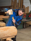 Carpenter with mallet and chisel. In his workshop Royalty Free Stock Image