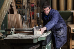 Carpenter man cutting wood with tablesaw. Portrait of Carpenter man cutting wood with tablesaw in workshop Stock Image