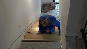 Carpenter man install stairs board and show finger up smiling looking at camera. Handheld shot stock video