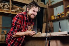 Carpenter man`s hand treats the tree, cuts the shavings. stock photos