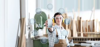 Carpenter man show the mobile phone with empty symbol icons on carpentry background royalty free stock image