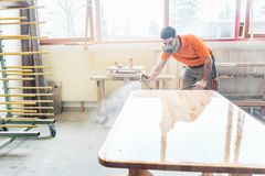 Carpenter man spraying varnish on a table he works on Royalty Free Stock Images