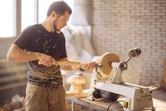 Man working at small wood lathe, an artisan carves piece of wood. Carpenter man working at small wood lathe, an artisan carves piece of wood using manual lathe Stock Photography