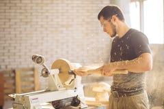 Man working at small wood lathe, an artisan carves piece of wood. Carpenter man working at small wood lathe, an artisan carves piece of wood using manual lathe Stock Image